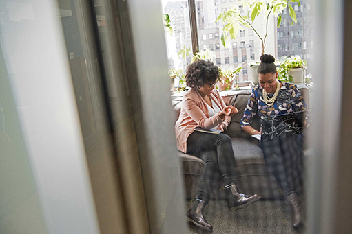 Two women talking and sitting on a couch with their pen, notebook and laptop